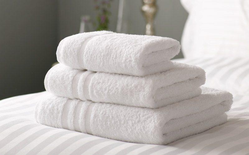 Three folded crisp white luxury range towels on wide stripe bedlinen