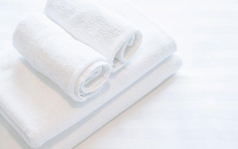 crisp white towels on a wide stripe duvet cover